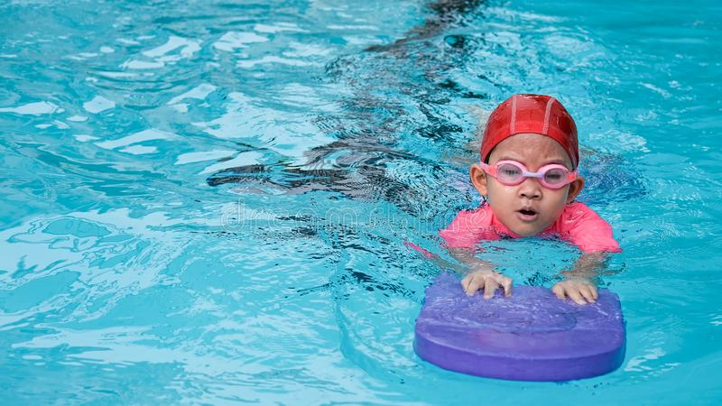 Kid learn how to swim in swimming class.  stock images