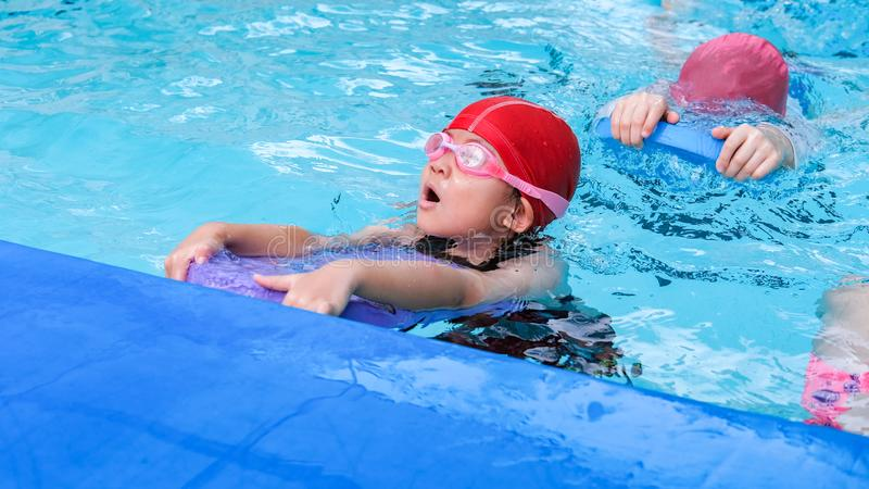Kid learn how to swim in swimming class.  royalty free stock photography