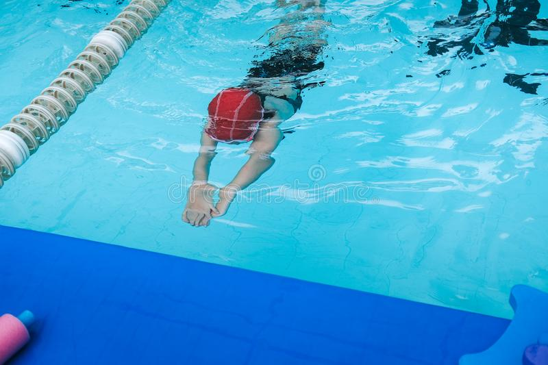 Kid learn how to swim in swimming class. Under water stock photography