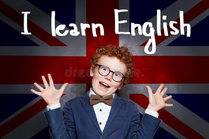 Kid learning English. Young boy pupil on the UK flag background stock photo
