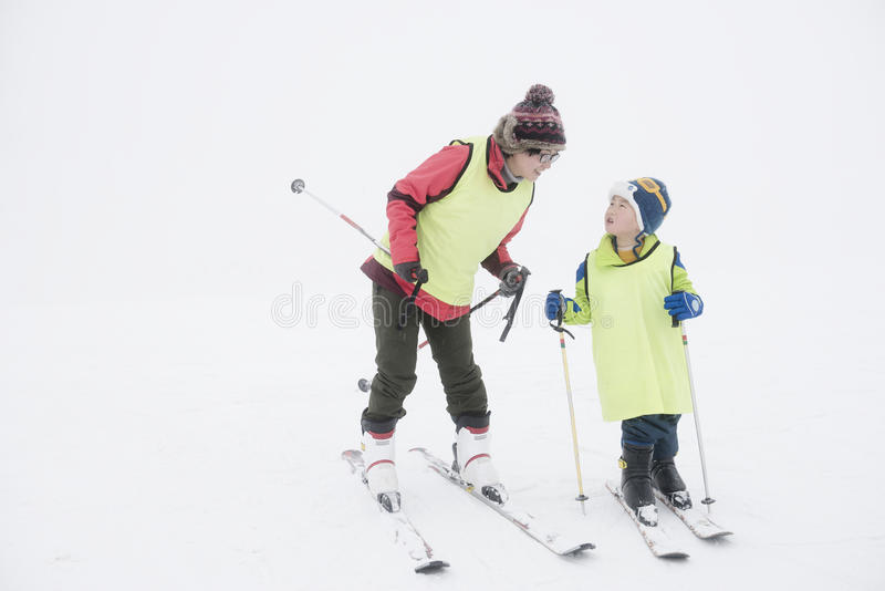 Kid learning ski. Chinese mom teaching son learn ski in winter