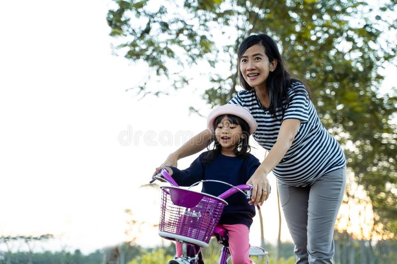 Kid learning to ride bicycle with mother royalty free stock images