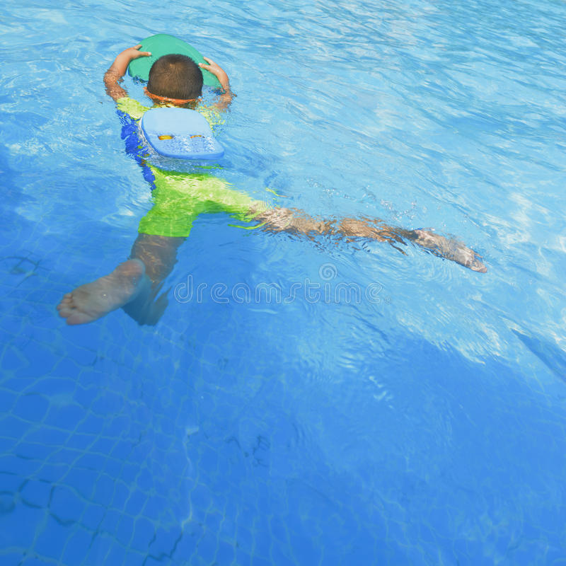 Kid learning to swim in summer. Chinese kid learning to swim in pool at summer day stock photo