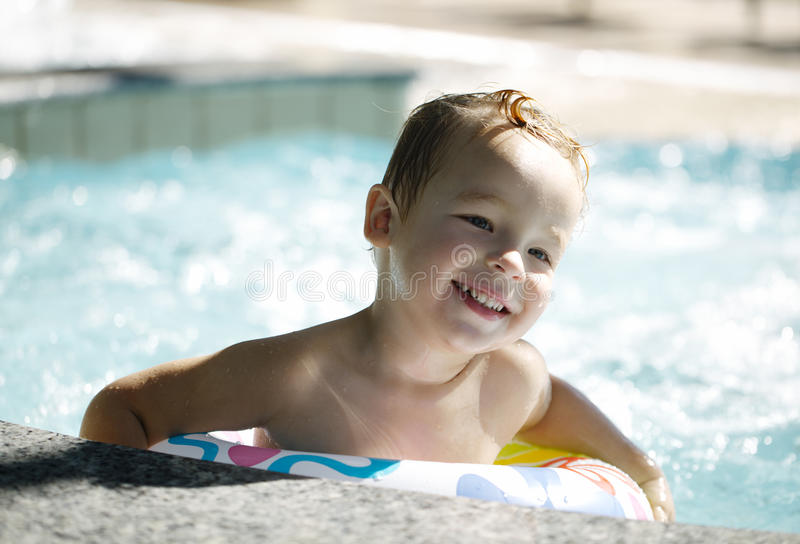 Kid learns to swim using a plastic water ring. Smiling kid learns to swim using a plastic water ring in the swimming pool or waterpark royalty free stock photo