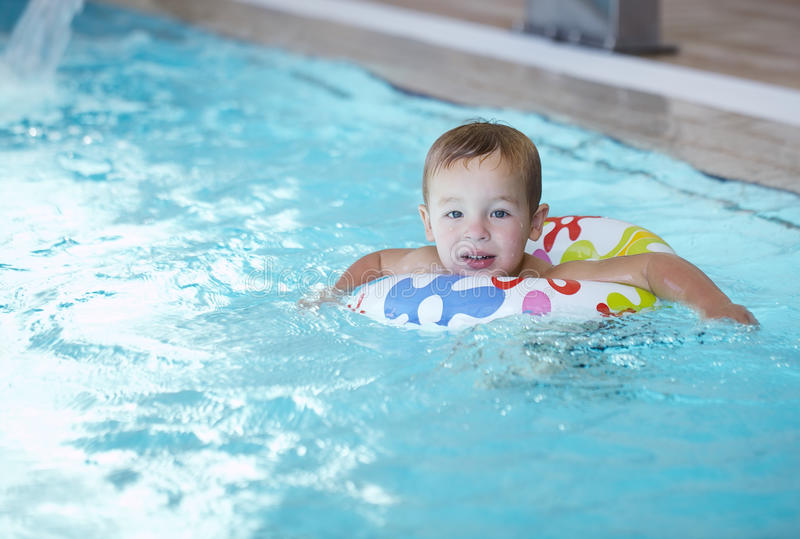 Kid learns to swim using a plastic water ring. In the swimming pool or waterpark stock photos