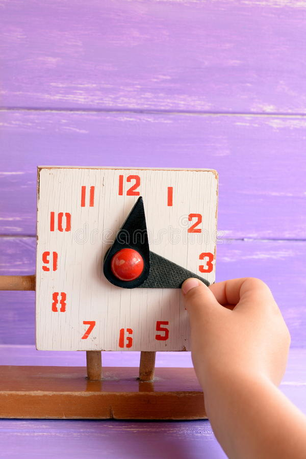 Kid learns to tell time on old wooden clock toy. Child pulls a hand to translate the time royalty free stock photography