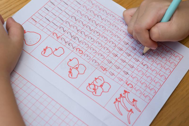 Kid learns to write Arabic numerals by following guide. S royalty free stock photo