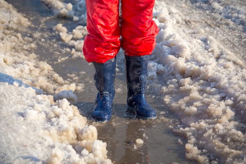 Kid legs in rainboots standing in the ice puddle royalty free stock photography