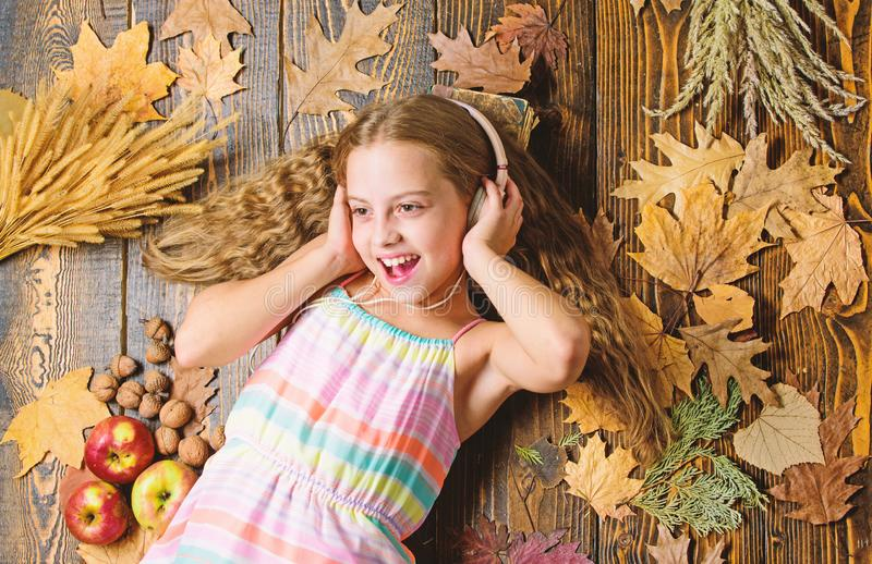 Kid listen music headphones wooden background. Child listen music relaxing top view. Fall melody concept. Fall music. Playlist. Best songs about fall. Enjoy stock images