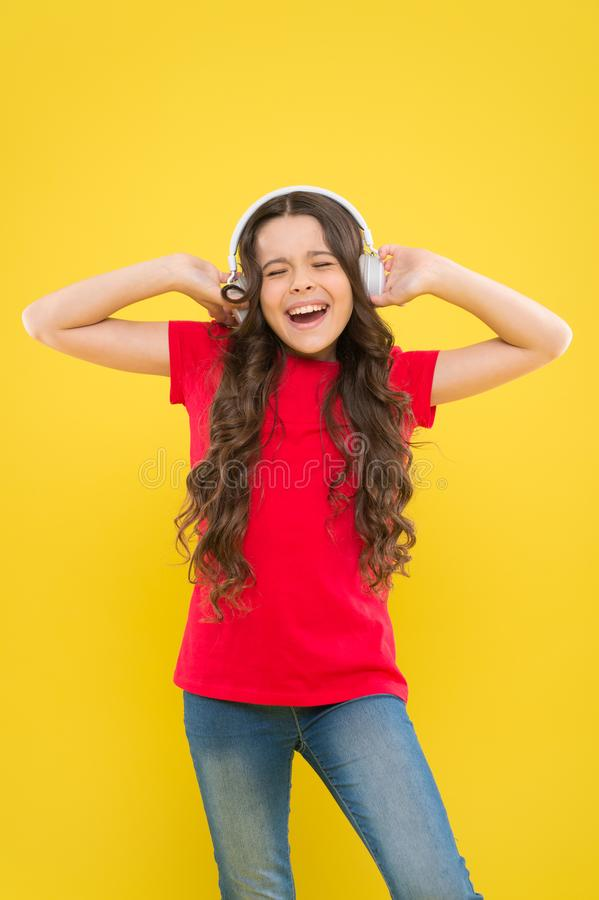 Kid listening music headphones. Music beat concept. Entertainment and fun. Top summer songs. Child or teen enjoy music. Playing in earphones. Little girl stock images