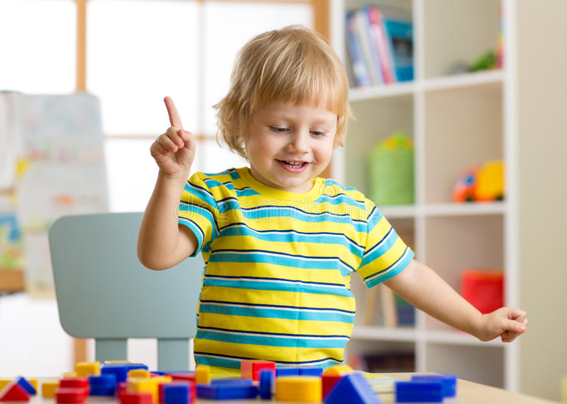 Kid little boy learning shapes, early education and daycare concept stock photography