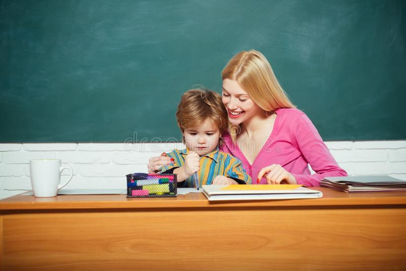 Kid little boy and teacher woman pedagogue classroom. Developing and upbringing. School kindergarten and development stock photography