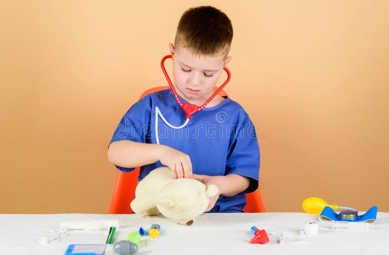 Kid little doctor busy sit table with medical tools. Medical examination. Medicine concept. Medical procedures for teddy. Bear. Boy cute child future doctor royalty free stock images