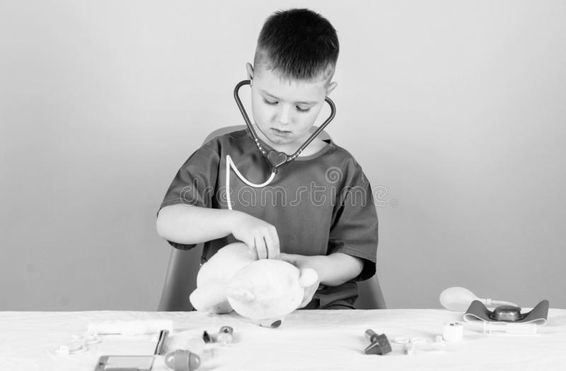Kid little doctor busy sit table with medical tools. Medical examination. Medicine concept. Medical procedures for teddy. Bear. Boy cute child future doctor stock photo