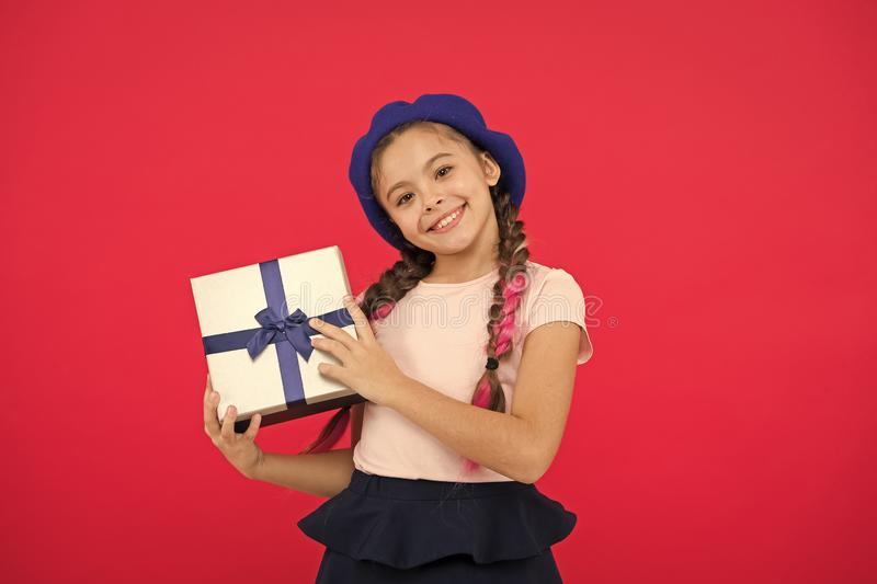 Kid little girl in beret hat hold gift box. Child excited about unpacking gift. Small cute girl received gift pack with. Ribbon bow. Guess what your child dream stock photos