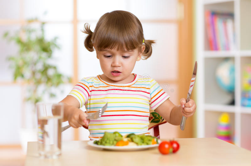 Kid little girl eats vegetarian food at home stock photo