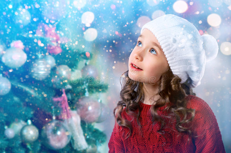 Kid little girl near Christmas tree. New Year card royalty free stock image