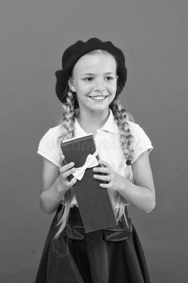 Kid little girl in school uniform and beret hold gift box. Child excited about unpacking gift. Small cute girl received. Holiday gift. Spread happiness. Best royalty free stock photo