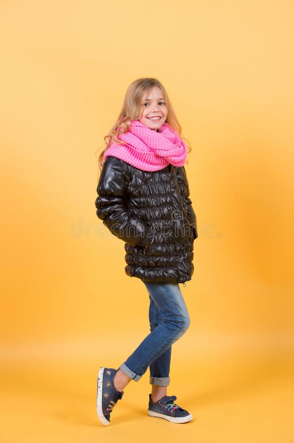 Kid with long blond hair black coat, scarf, jeans, sneakers stock photography