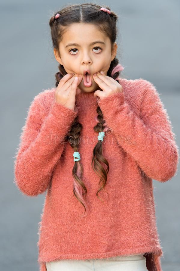 Kid with long braided hair make bored grimace face. So boring. Bored girl going crazy. Play with facial expressions royalty free stock images
