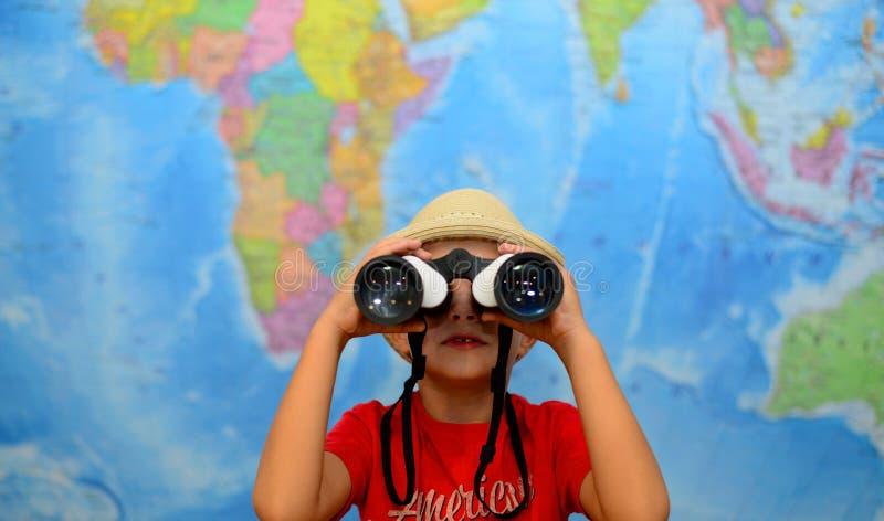 Kid is looking through binoculars around. Adventure and travel concept. Joyful background. stock photos