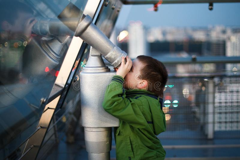 Kid is looking through a telescope. The boy is looking through a telescope royalty free stock photos