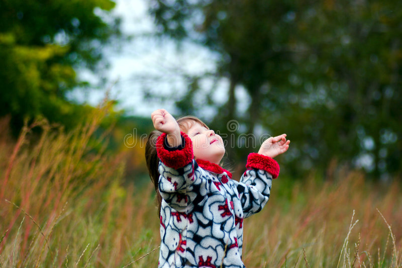 Kid looking up to the sky. In the autumn meadow stock photo
