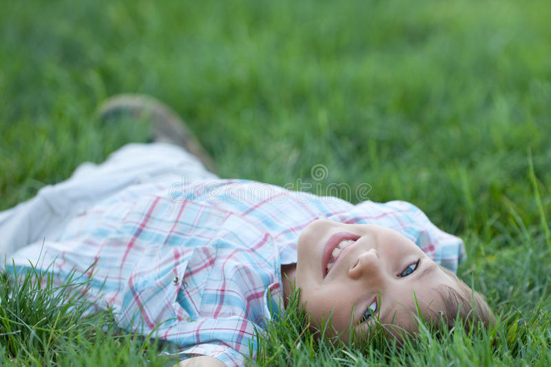 Kid lying in the green grass royalty free stock images
