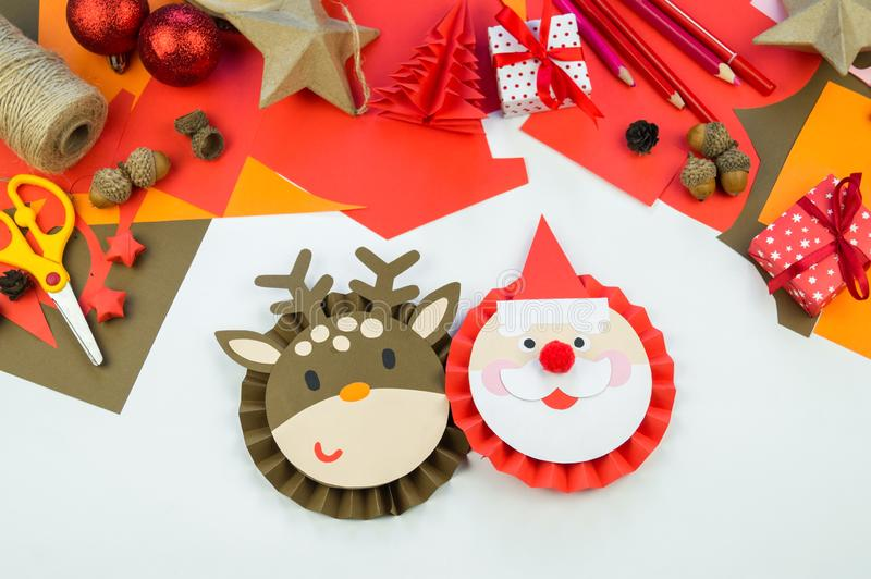 Kid makes a deer and santa claus out of paper stock images