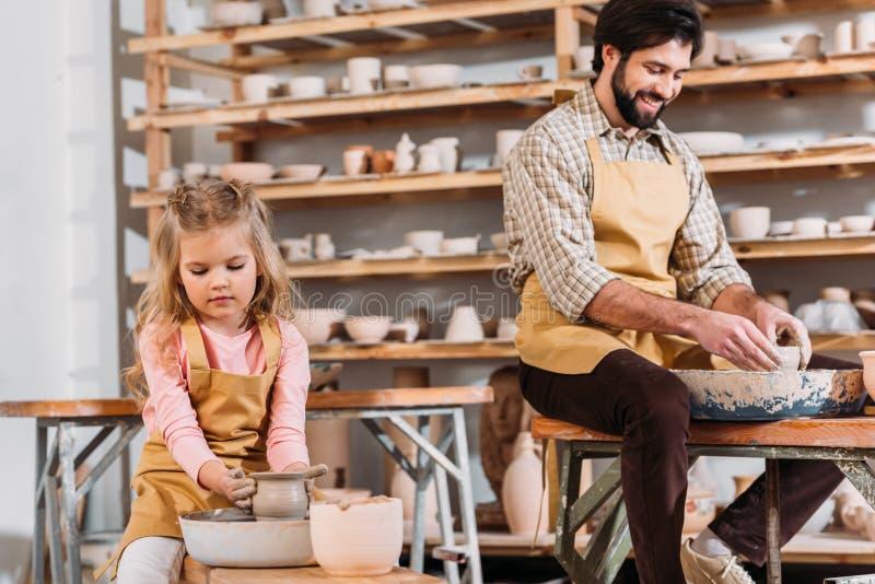 kid making ceramic pot on pottery wheel with teacher royalty free stock photos