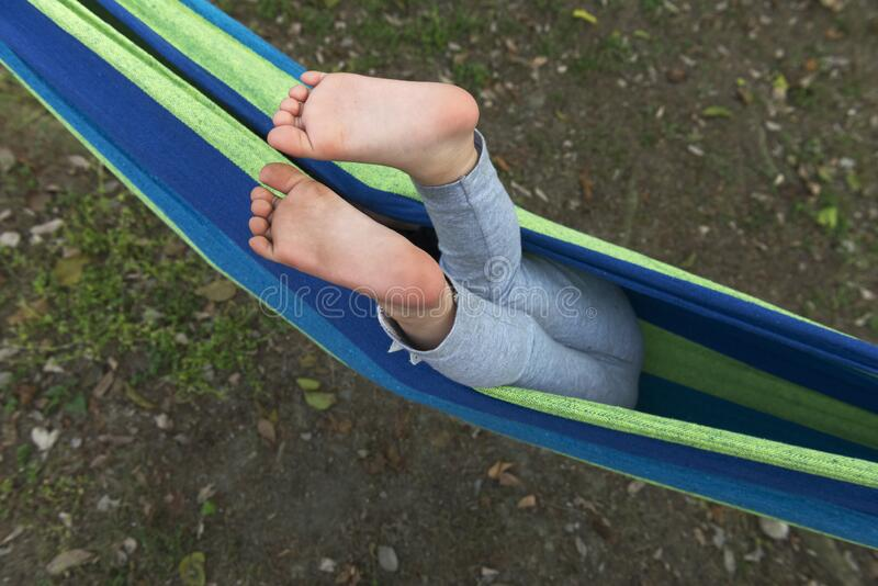 Bare feet on hammock. Kid making fun , bare feet on hammock, wrap face. from high viewpoint royalty free stock photo
