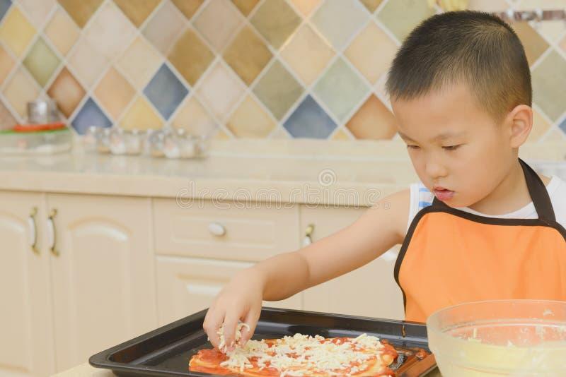 Kid making pizza royalty free stock photo