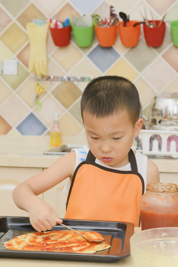 Kid making pizza stock images