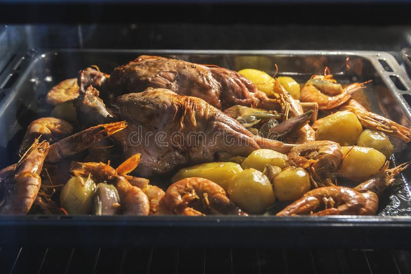 Kid meat baked in the oven with some potatoes, prawns, shrimps and vegetables. Family event and gathering dinner. With empty copy space for Editor`s text stock photography