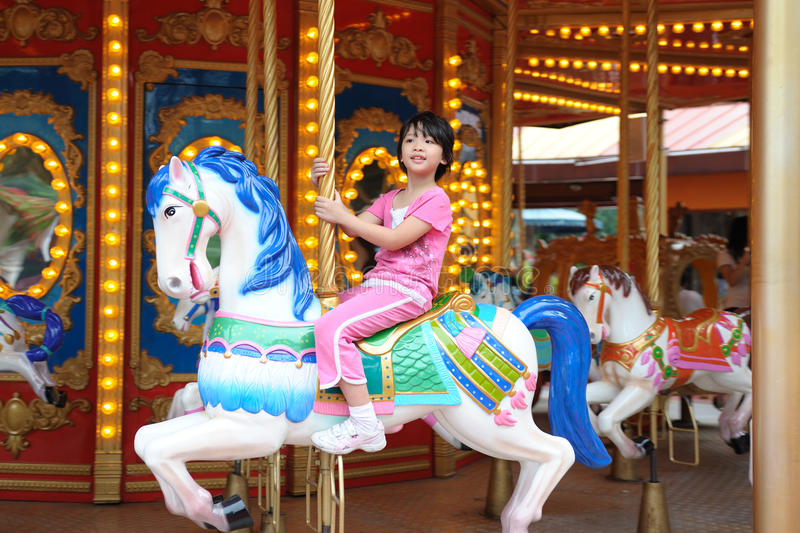Kid in Merry go Round. Asian kid playing in Merry go Round royalty free stock photography
