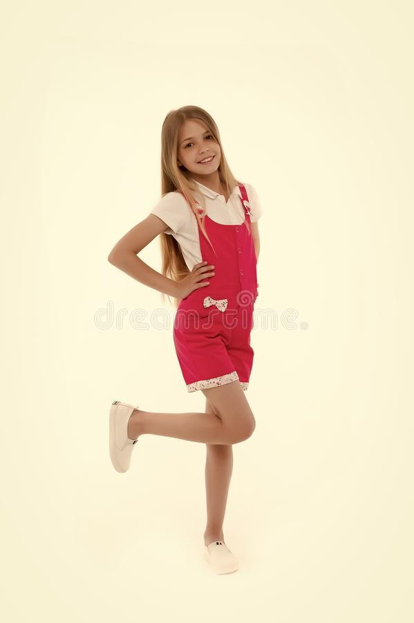 Kid model in fashionable overall. Small girl smile in pink jumpsuit isolated on white. Child smiling with long blond stock photos