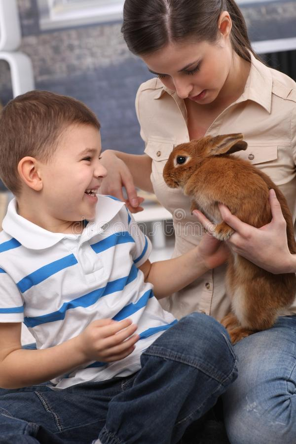 Kid and mom with pet rabbit at home. Laughing kid and young mom playing with pet rabbit at home stock photos