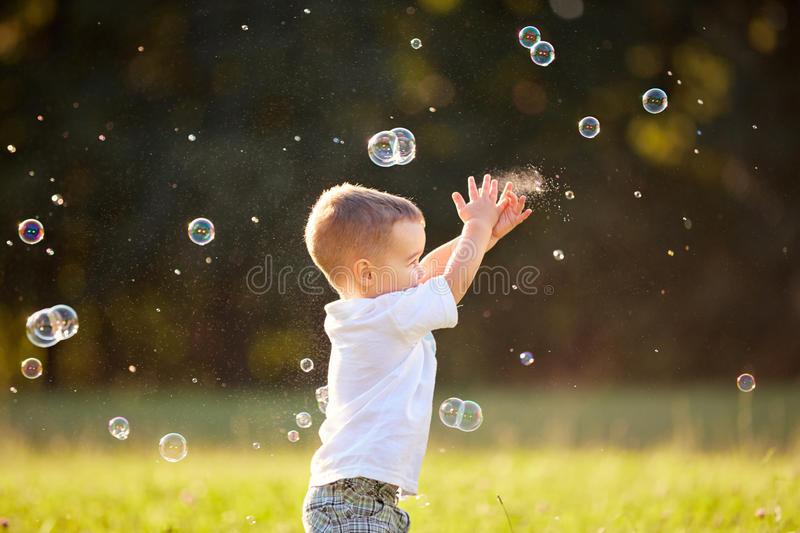 Kid in nature reaching soap bubbles stock images