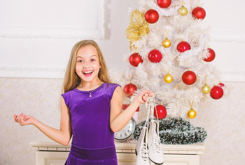Kid near christmas tree hold skates gift. Little girl satisfied christmas gift. Best gift ever. Happy new year concept royalty free stock photo