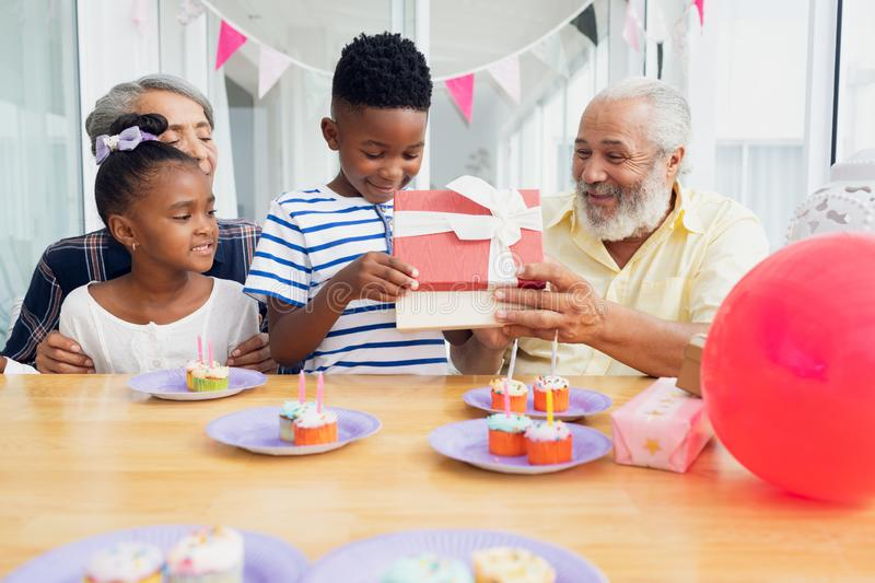 Kid opening gift while family watches royalty free stock photography