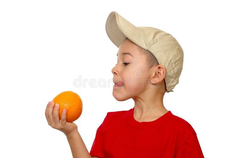 Kid and orange. Seven year old boy smiling holding an orange and licking his lips, isolated on white background royalty free stock photo