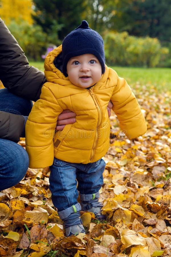 Kid in the orange jacket keeps mum royalty free stock image