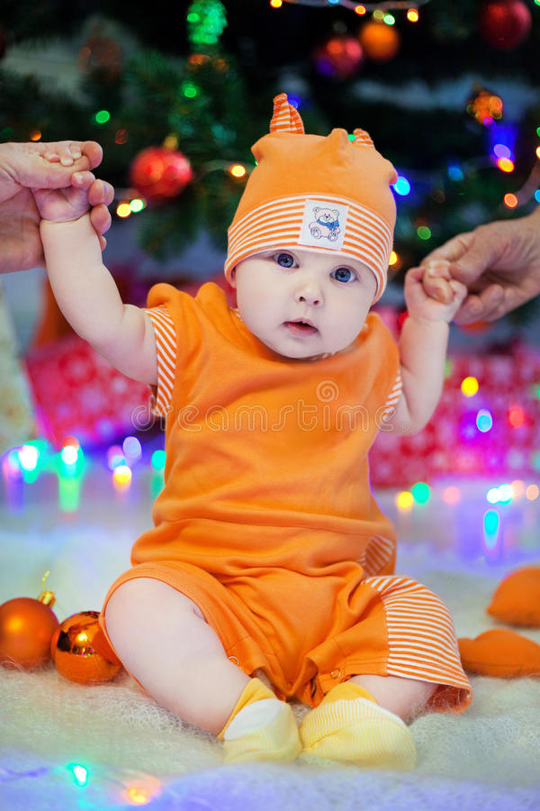 Kid in orange suit on a background of the Christmas tree lights and holding the hands of parents. Kid in an orange suit on a background of the Christmas tree royalty free stock photo