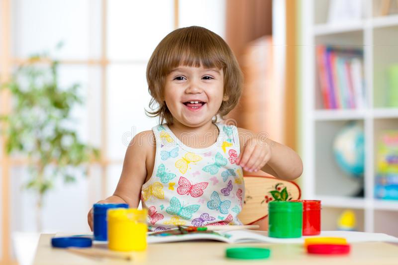 Kid painting in daycare or playschool. Pretty child girl painting with colours in daycare or playschool royalty free stock photo