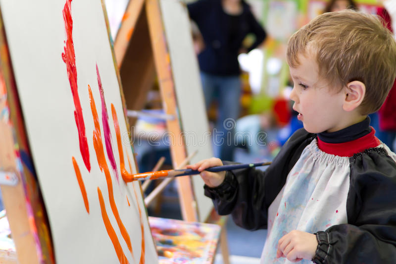 Kid painting at preschool. Preschool boy painting with colourful paint at preschool stock photo