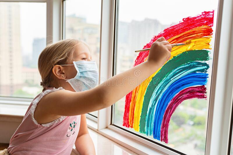Kid painting rainbow during Covid-19 quarantine at home. Girl near window. Stay at home Social media campaign for coronavirus. Prevention, let`s all be well