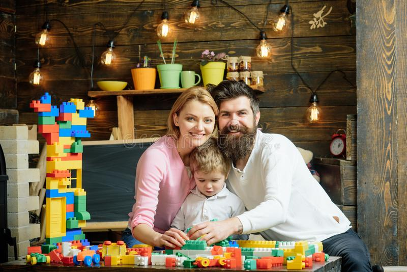 Kid with parents play with plastic blocks, build construction. Father, mother and cute son play with constructor bricks royalty free stock images