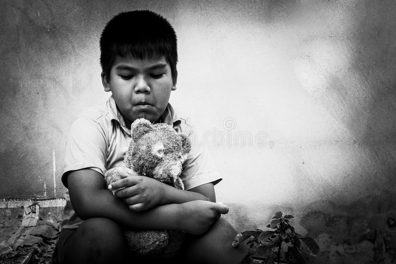 Kid pauper with old teddy bear. Sitting near the concrete wall,black and white tone royalty free stock photography