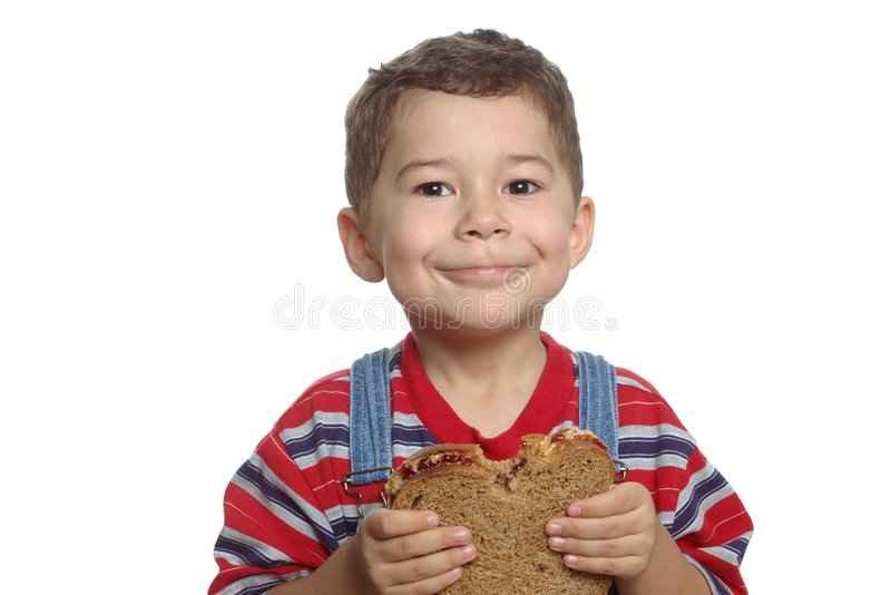 Kid and peanut butter. A 5 year old hispanic boy holding a peanut butter and jelly sandwich with a bite taken out of it, on whole wheat bread, isolated on white stock photography