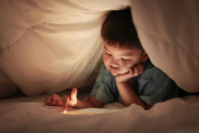 Kid play internet online game, under duvet. Little boy kid using tablet play internet online game, finger hand pointing at touchscreen, while lying under white royalty free stock photography